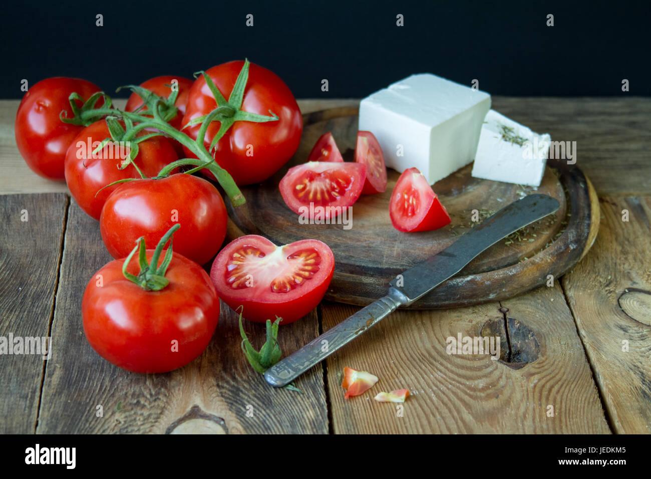 Les tomates et fromage grec blanc sur une planche de bois. Photo Stock