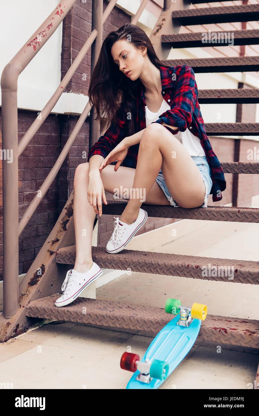 Belle jeune femme en chemise à carreaux et jeans taille basse short shorts  et baskets blanches 108bc8d13e3