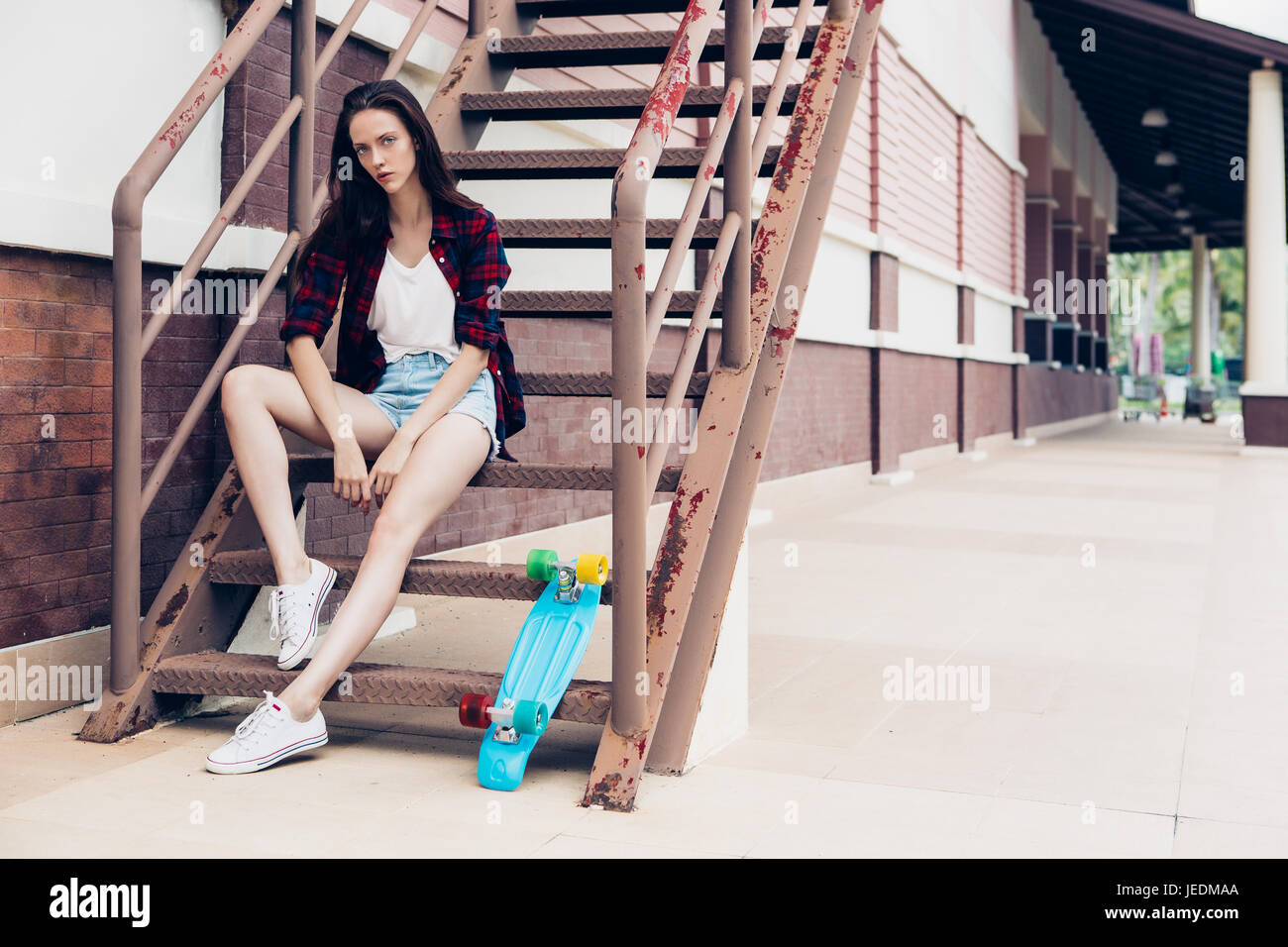 Belle jeune fille en chemise à carreaux et jeans taille basse short shorts  et baskets blanches c9280cffd81