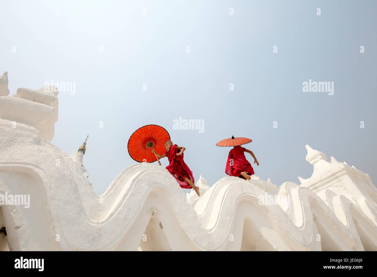 Moines avec parapluie Pagode Hsinbyume Temple à Mandalay Myanmar région Mingon Myanmar pagode temple blanc Photo Stock