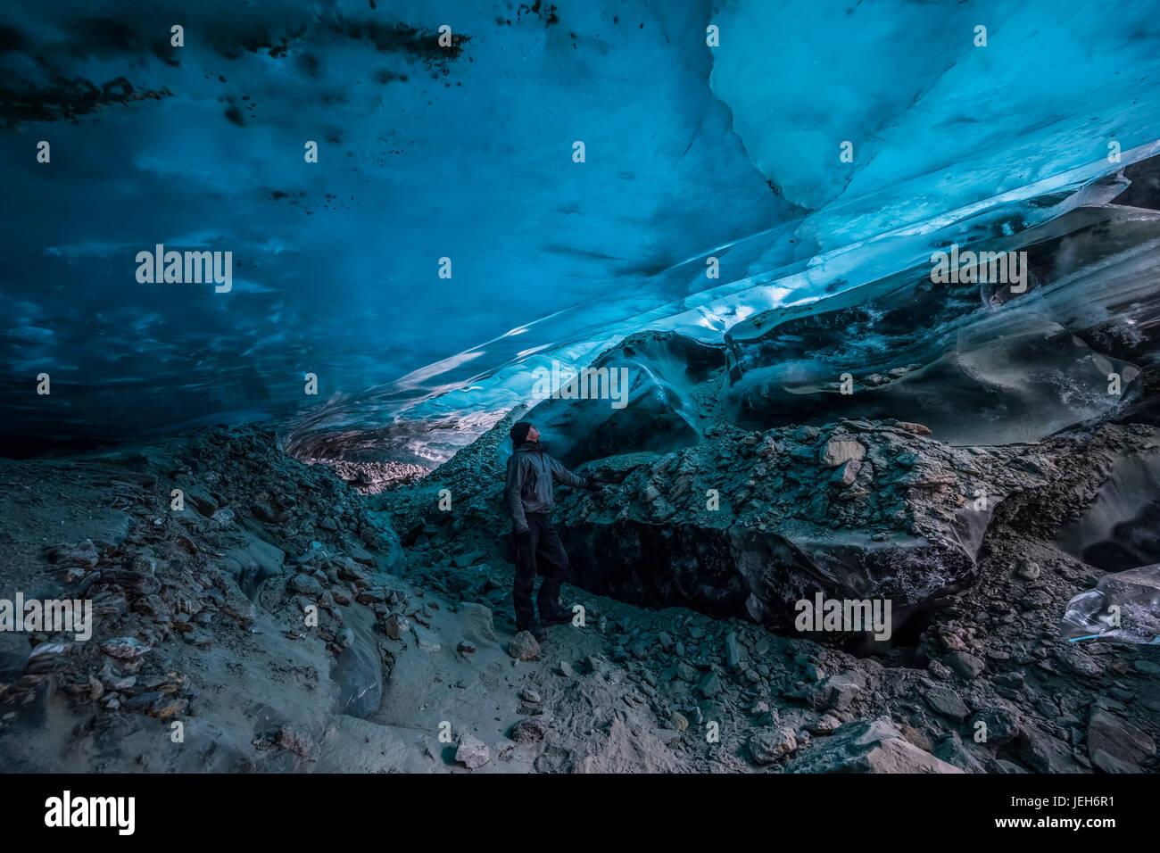 Un homme regarde la glace bleu translucide d'une grotte de glace du glacier Canwell; Alaska, États Photo Stock