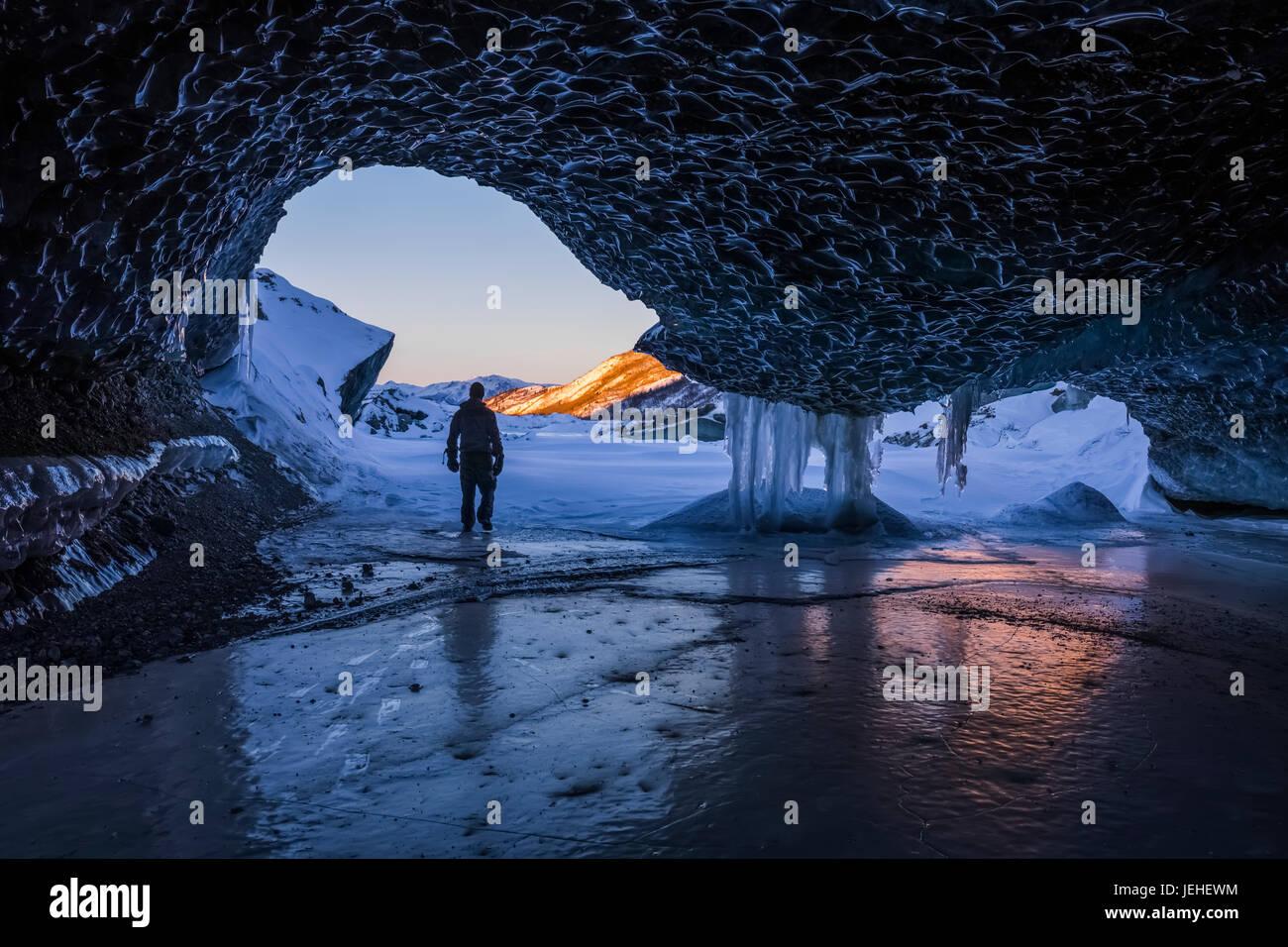 Un homme marche à l'entrée d'un tunnel de glace au terminus de Canwell Glacier dans la chaîne Photo Stock