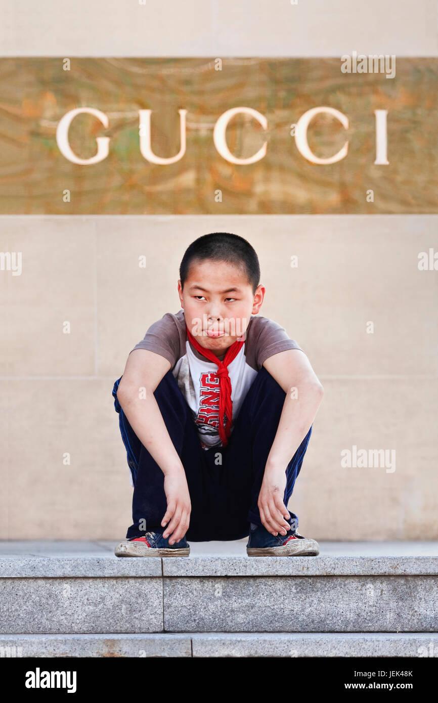 c369ff40ab1c87 Garçon accroupi en face d une boutique Gucci. La Chine est devenue le  premier ministre de long terme du marché des produits de luxe.
