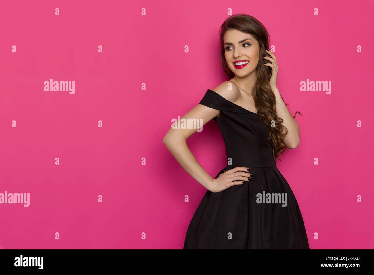 3c50bd66ef4 Belle jeune femme élégante en robe de cocktail noire est à l arrière sur l