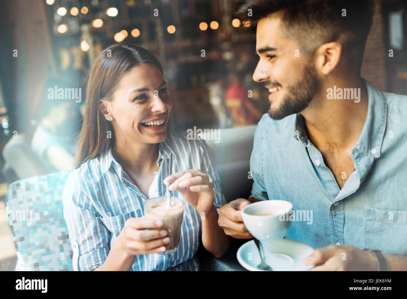 Young attractive cheerful couple on date in coffee shop Photo Stock