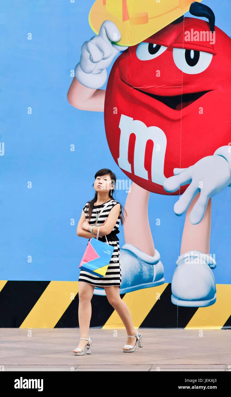 SHANGHAI - 4 juin 2014. Jeune chinoise en face de M&M'€™s billboard. M&M'€™s est la marque numéro Photo Stock