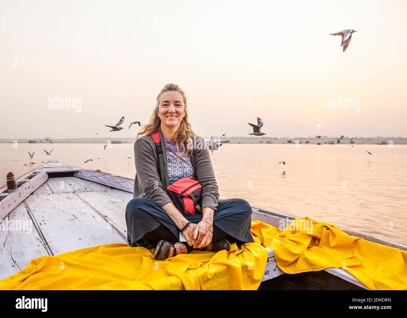 Portrait d'une touriste à cheval sur un bateau à rames sur le Gange à Varanasi, Inde au lever Photo Stock