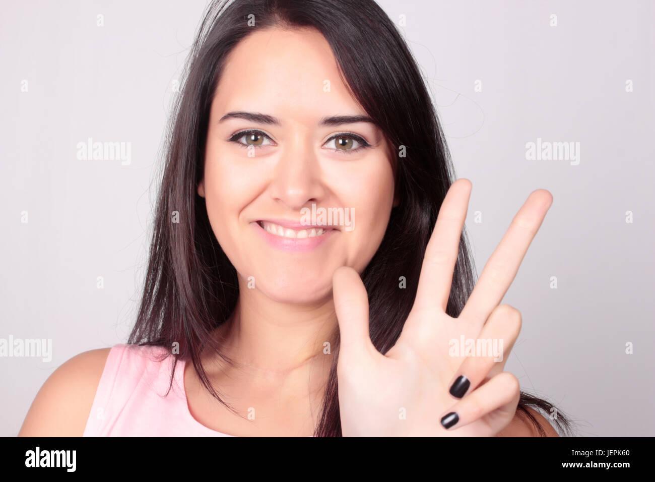 Belle jeune femme caucasienne comptant trois sur fond blanc. Comptage à la main, trois doigts. Photo Stock