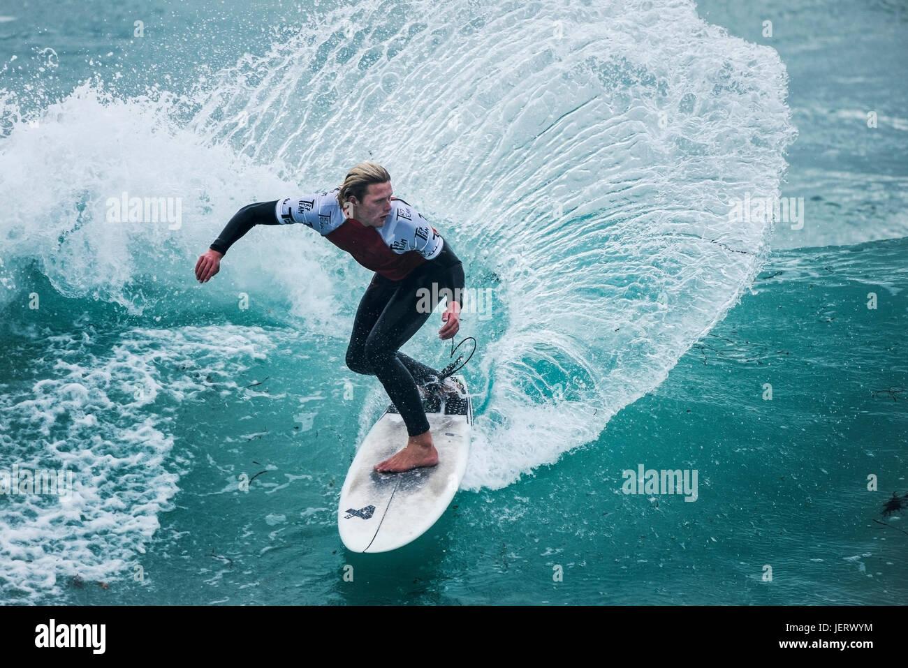 UK Surf. Action surf spectaculaire en tant que surfer rides une vague dans un concours à la plage de Fistral, Newquay, Cornwall Banque D'Images