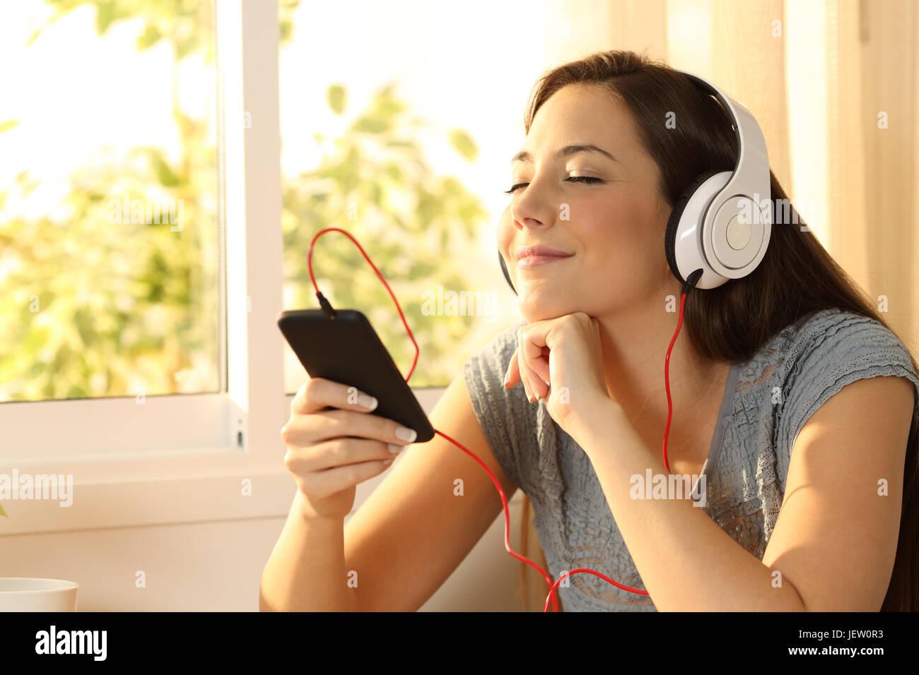 Relaxed woman listening music avec un casque et un téléphone intelligent à la maison avec une fenêtre à l'arrière-plan Banque D'Images