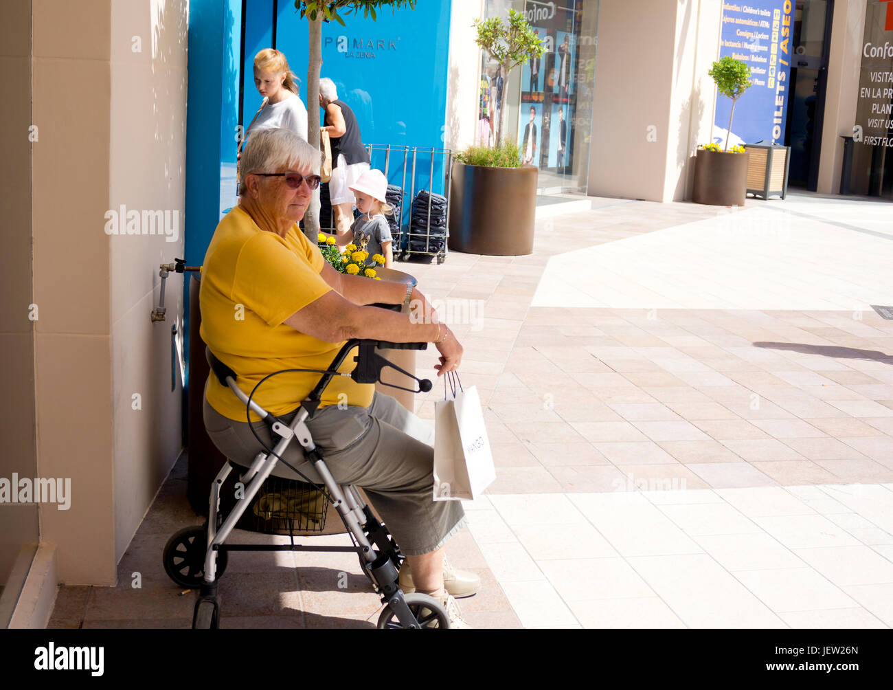 Femme avec aide à la marche assis à l'extérieur d'une boutique Photo Stock