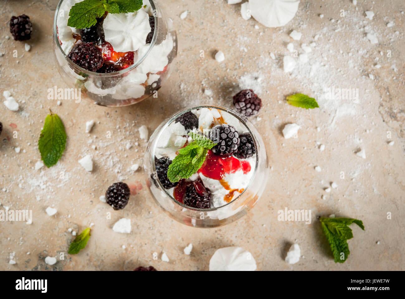 Dessert traditionnel anglais. Eton Mess - crème chantilly, meringue, mûres fraîches, sauce et caramel. Au service Banque D'Images