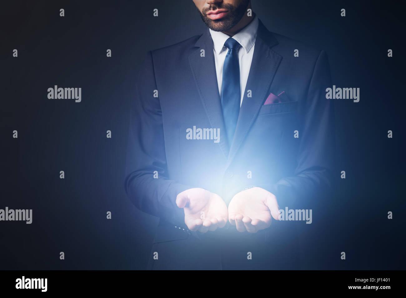 Lumière rayonnant à partir de businessman mains. Nouvelle idée, premier produit concept. Photo Stock