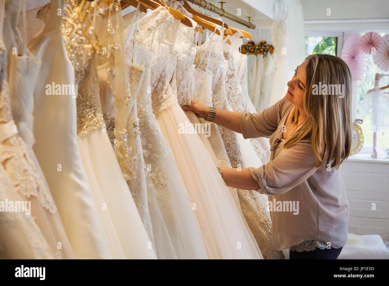 Un vendeur dans une boutique de robe de mariage, en regardant à travers les robes suspendues dans les rails. Photo Stock