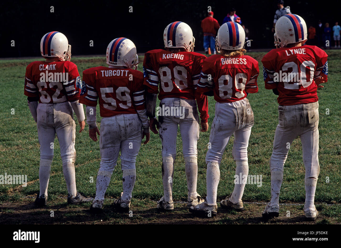 L'équipe de football le long de marge au cours de jeu avec dos à l'appareil photo en attente de Photo Stock