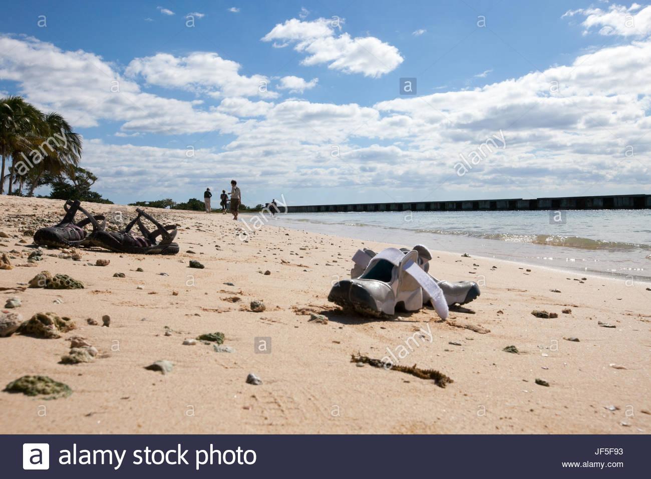 Deux paires de sandales s'asseoir dans le sable comme les touristes à pied la plage le long de l'océan Photo Stock