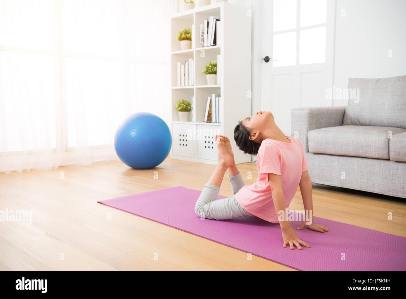Little Girl Doing Yoga Exercice Sur Tapis De Sol En Bois Avec Les
