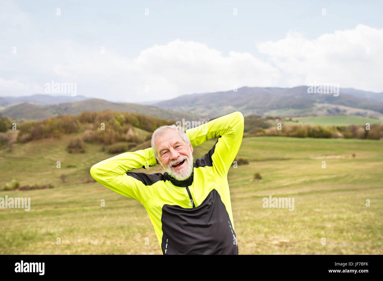 Senior runner à l'extérieur, sur de vertes collines doing stretching. Photo Stock