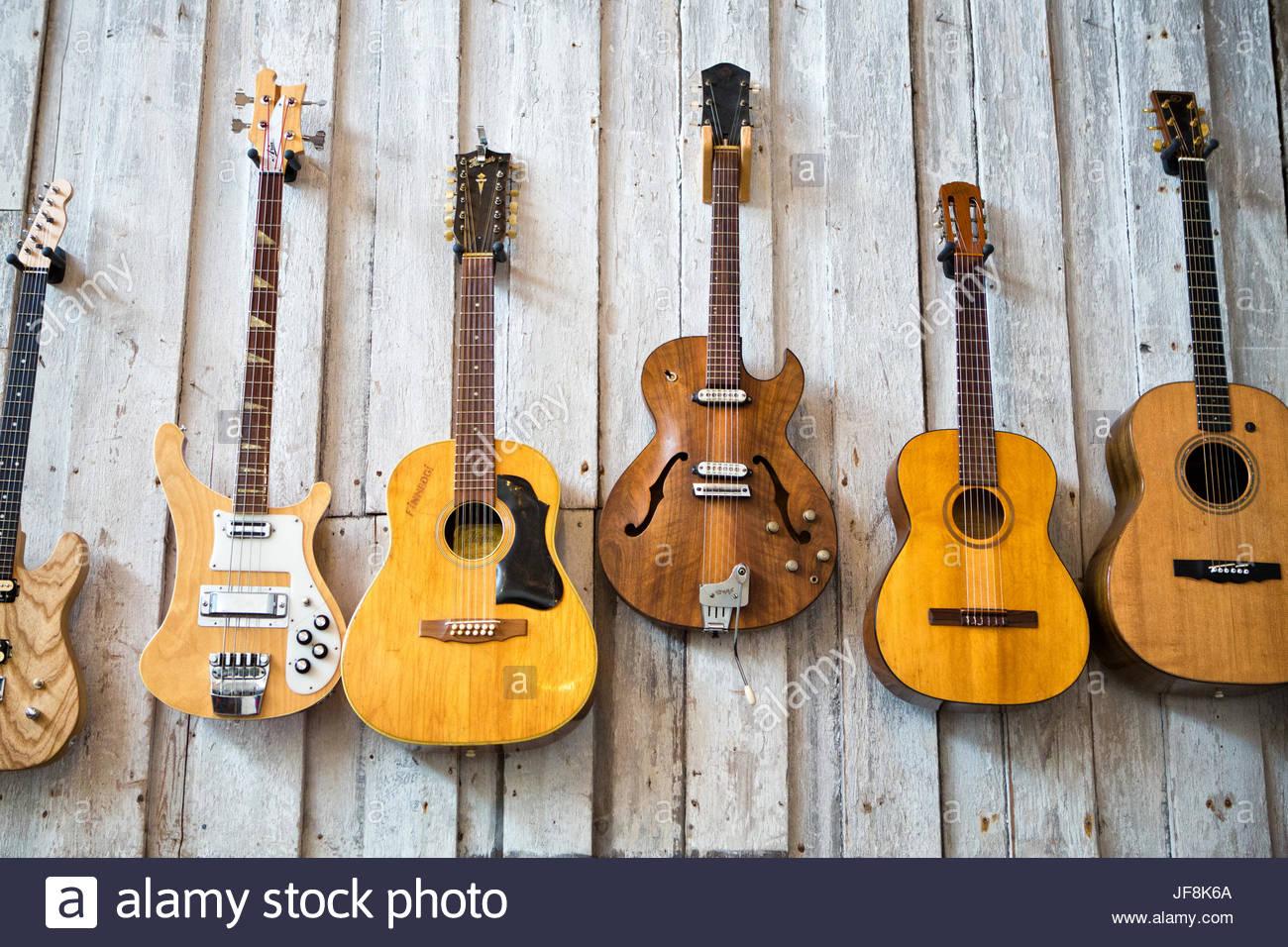 une collection de guitares accrocher sur le mur d'un producteur de