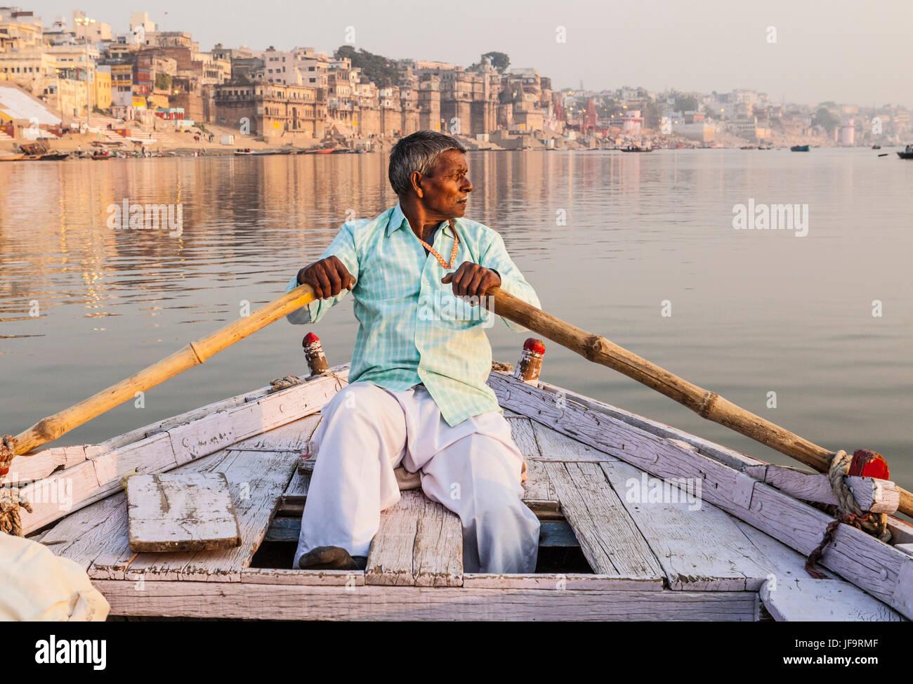 Un homme indien un bateau d'aviron pour les visites sur le Gange, Varanasi, Inde. Photo Stock