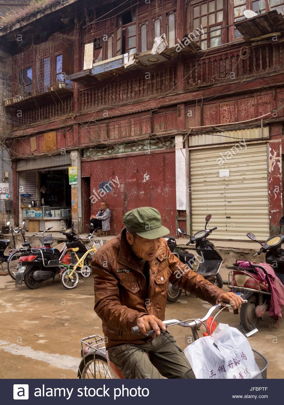Un homme vieux bâtiments délabrés cycles passé sur Street Guanghua. Photo Stock