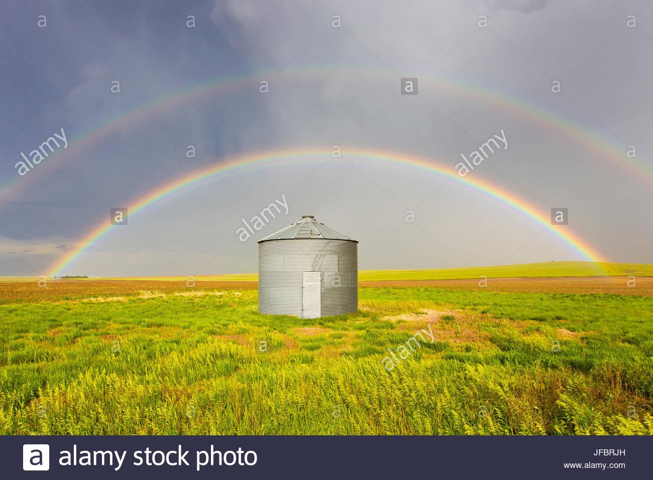 Un double arc-en-ciel est parfaitement centrée sur un silo à grains et champ de blé vert après Photo Stock