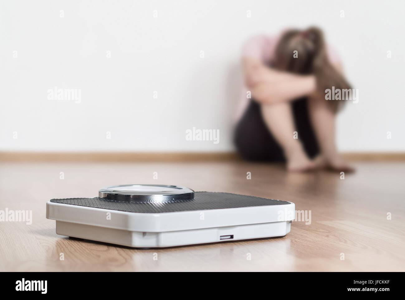 La perte de poids ne concept. Échelle et déprimé, frustré et triste woman sitting on floor holding Photo Stock