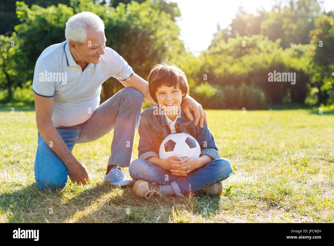 Grand passe-temps. Homme intelligent énergique dynamique prenant son grandkid dans le parc et en encourageant Photo Stock