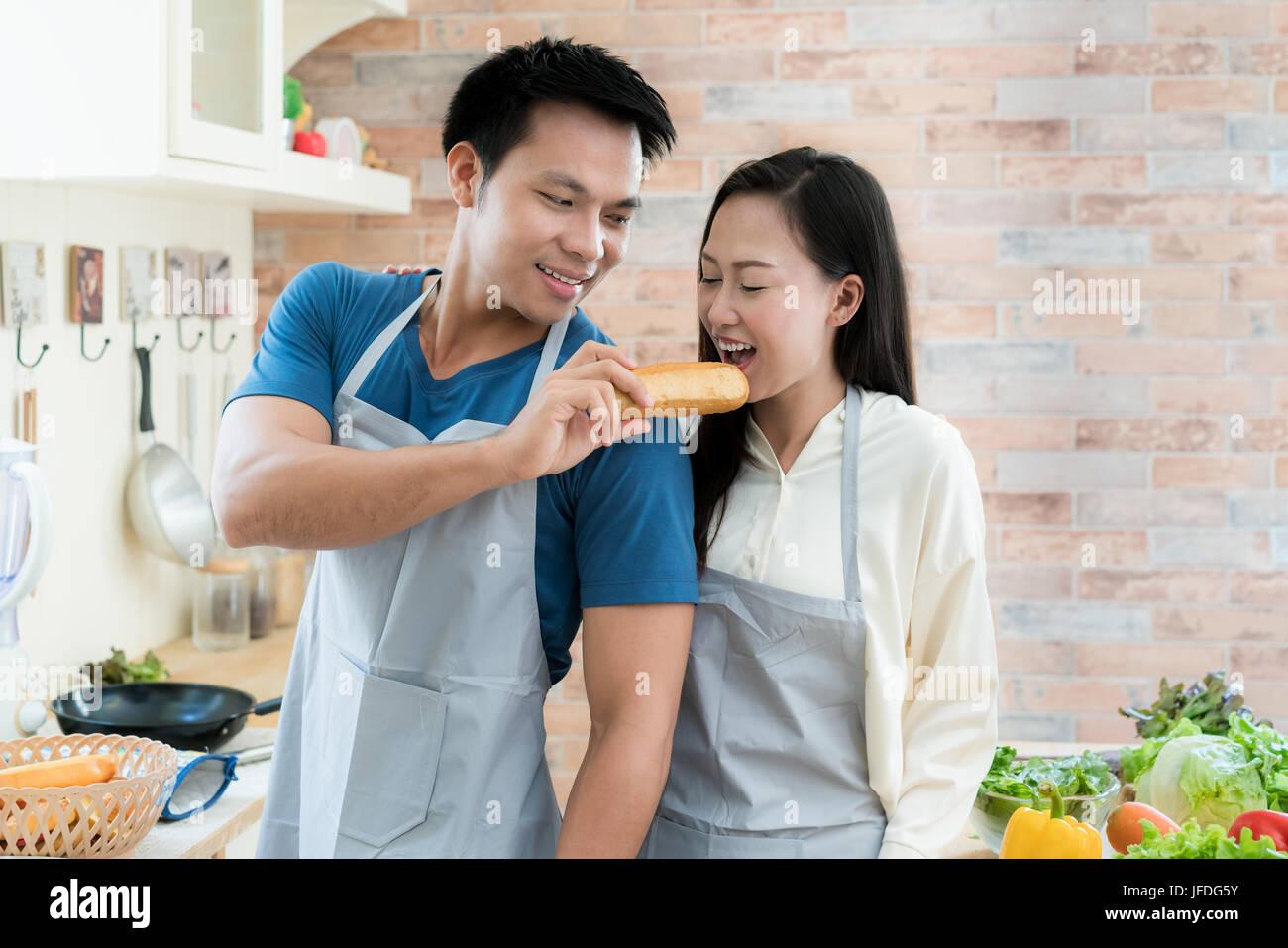 Belle asiatique jeune couple smiling pain alimentation pendant la cuisson dans la cuisine à la maison. L'amour Photo Stock