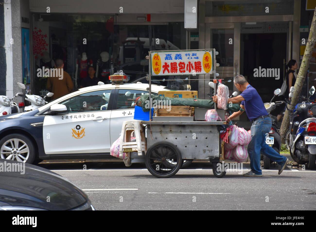 Un stand alimentaire personne pousse son panier au-delà d'un poste de police près de l'hôpital Mackay. Taipei, Taiwan. Banque D'Images