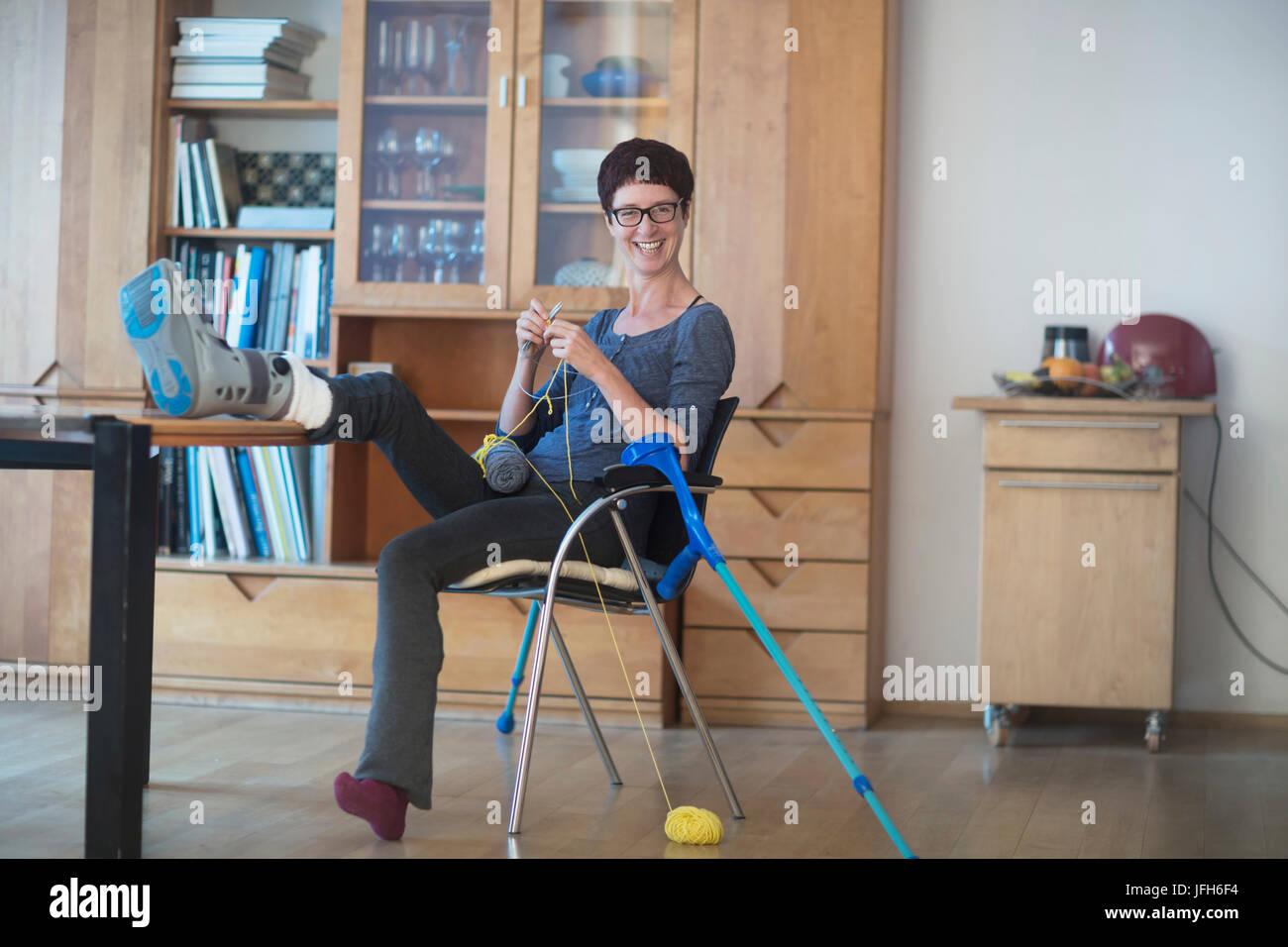 Woman jambe cassée sur table et de tricot à la maison Banque D'Images