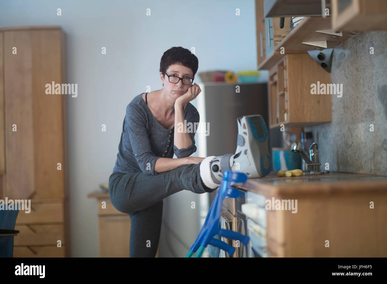 Portrait de femme posant sa jambe cassée sur le plan de travail de cuisine Banque D'Images