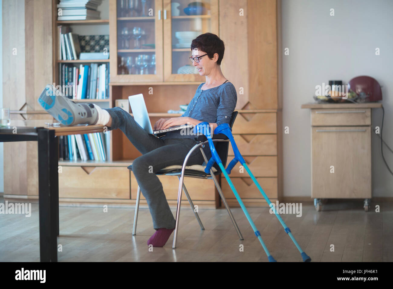 Femme posant sa jambe cassée sur table et à l'aide de l'ordinateur portable sur présidence Banque D'Images