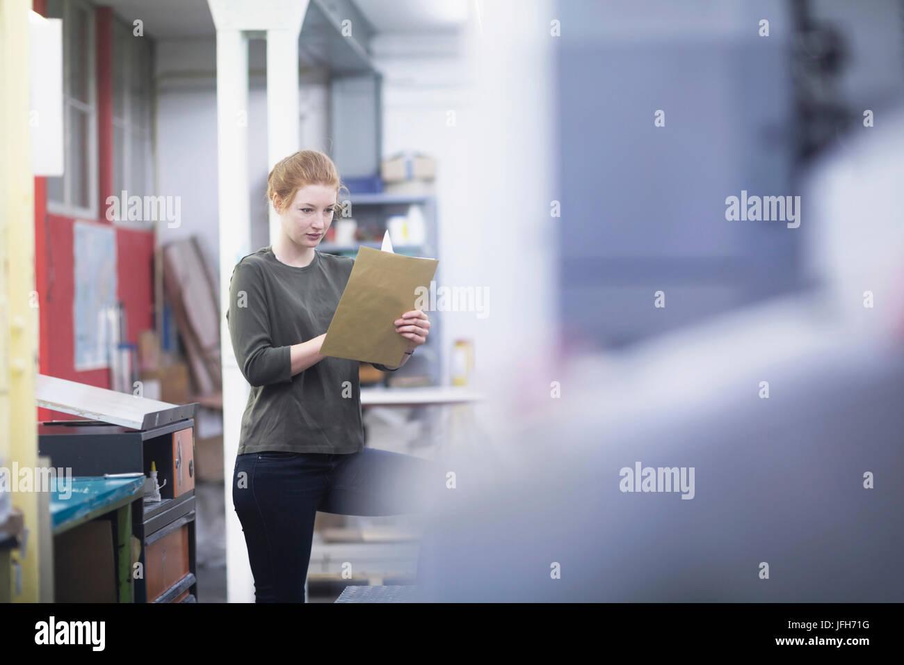 Femme lisant à papier imprimerie Banque D'Images