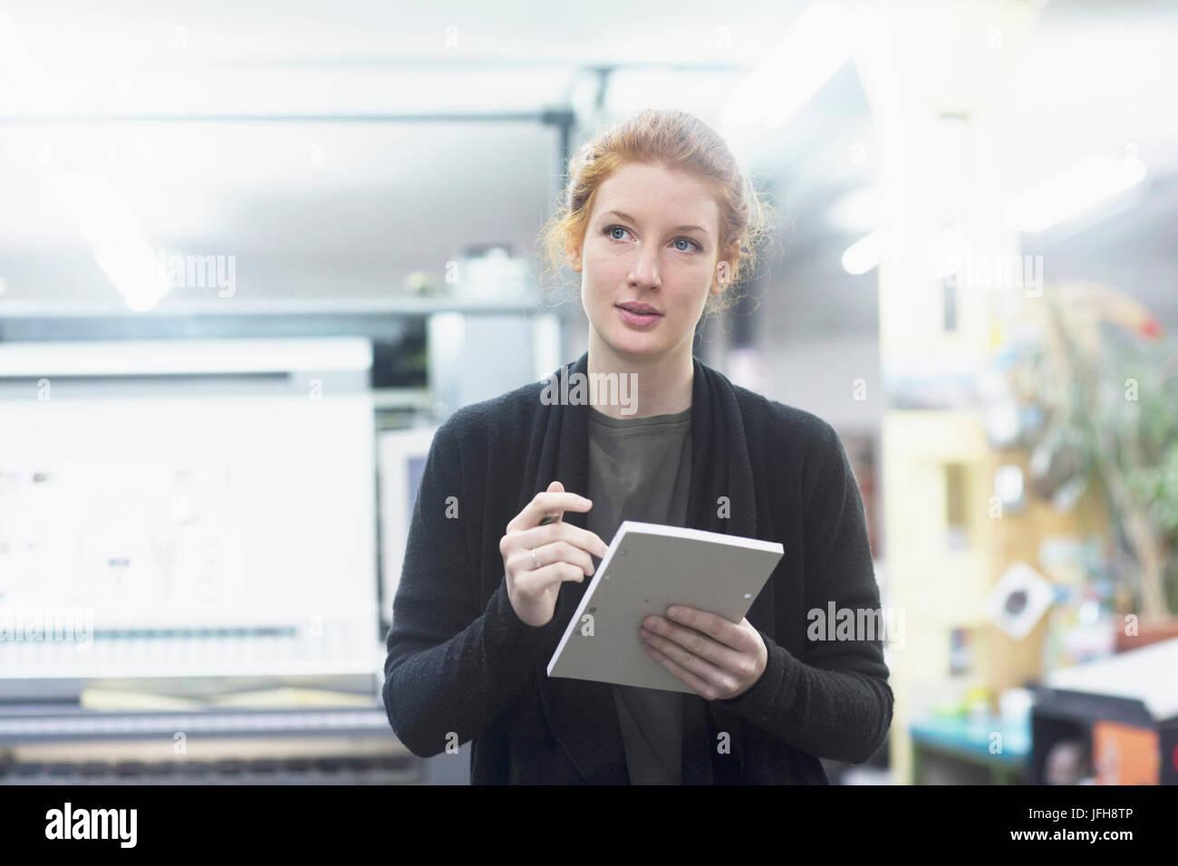 Travailleuse contemplative préparer la liste à la presse à imprimer Banque D'Images