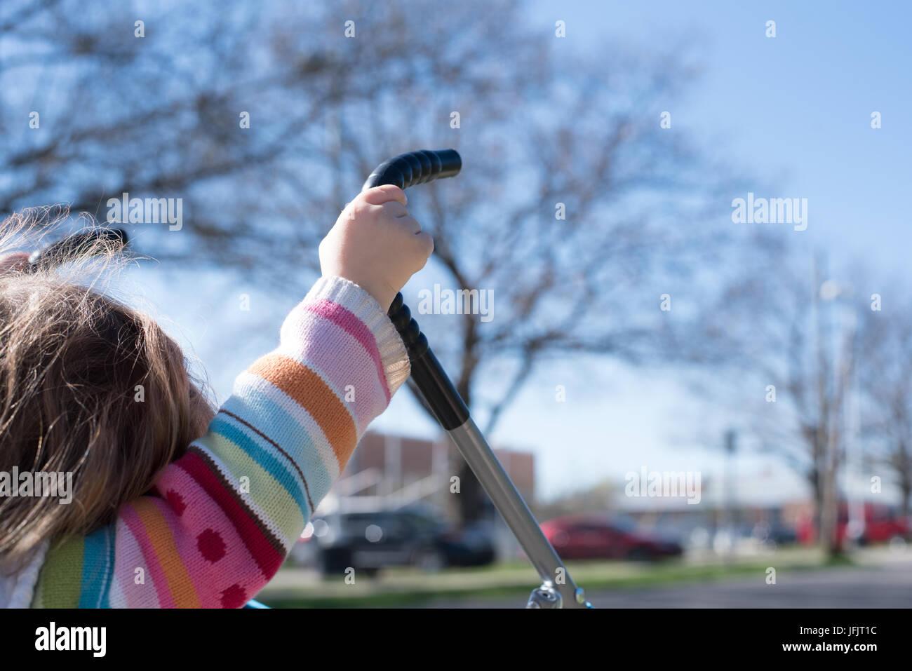 Une petite fille pousse une poussette avec juste sa petite main et la tête visible. De l'arrière. Photo Stock