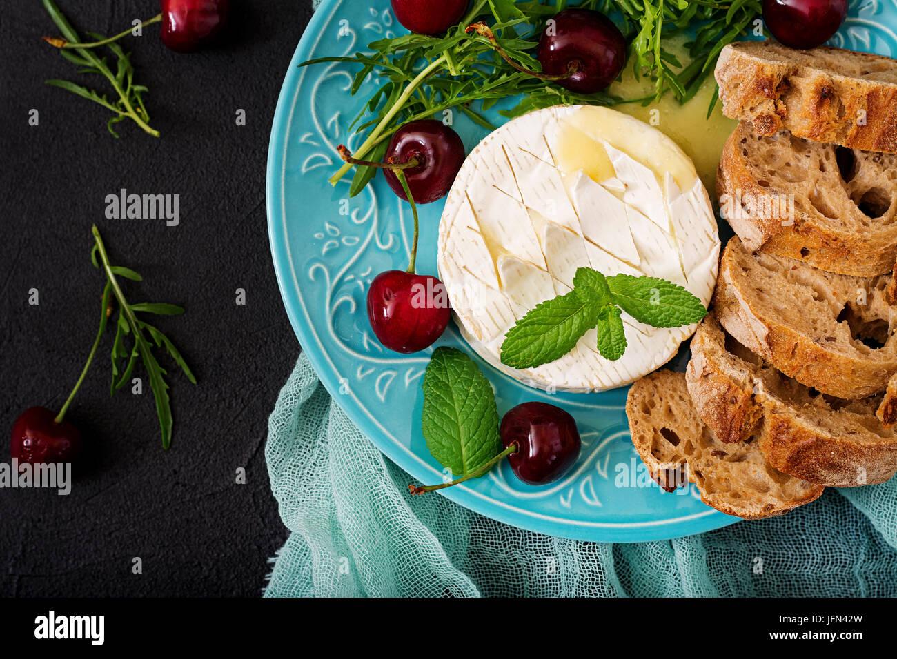 Camembert au four, grillé et salade de roquette avec la cerise douce. Mise à plat. Vue d'en haut Photo Stock