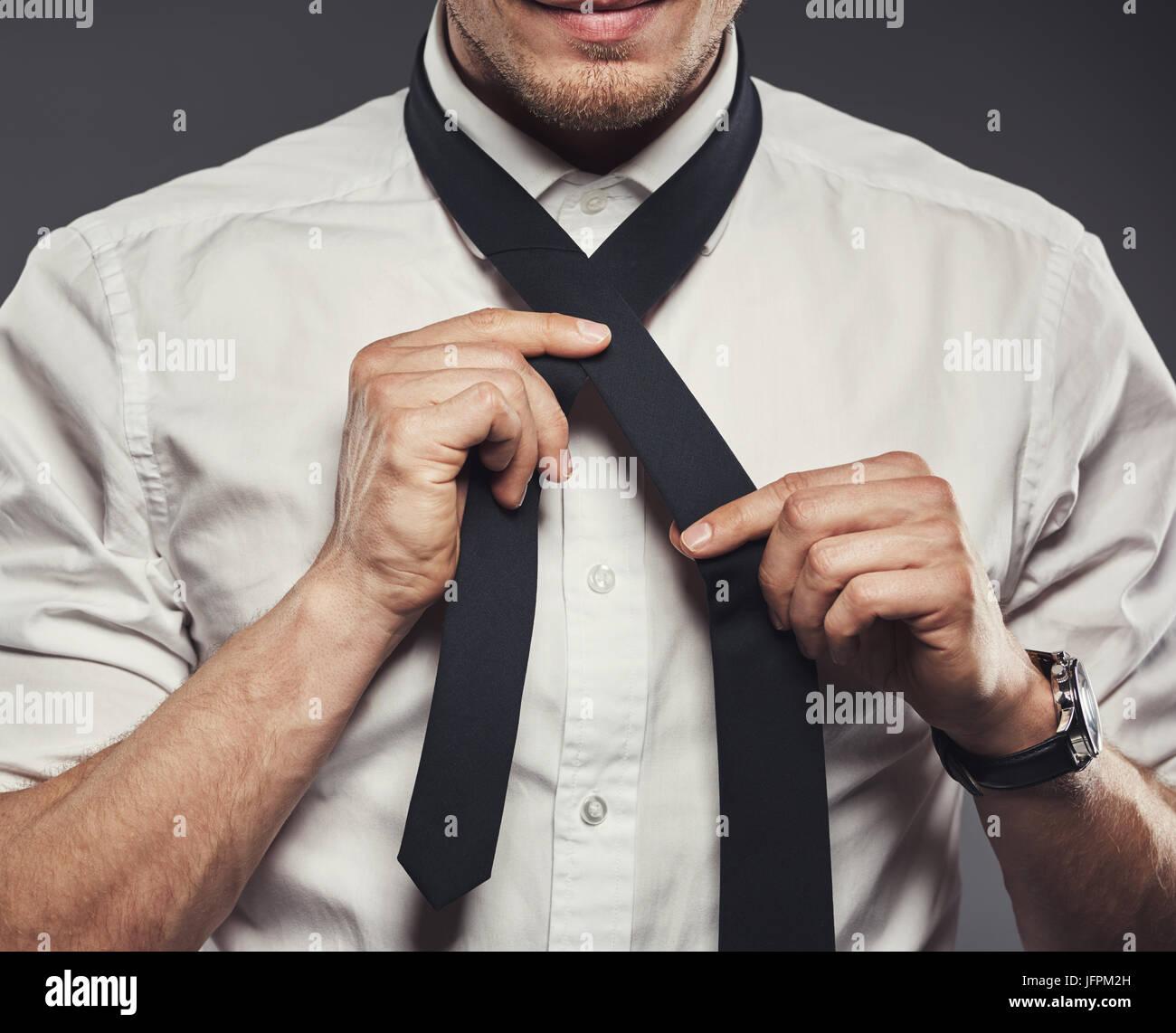 Libre d'un jeune homme dans une chemise debout dans un studio sur un arrière-plan gris lier sa cravate Photo Stock