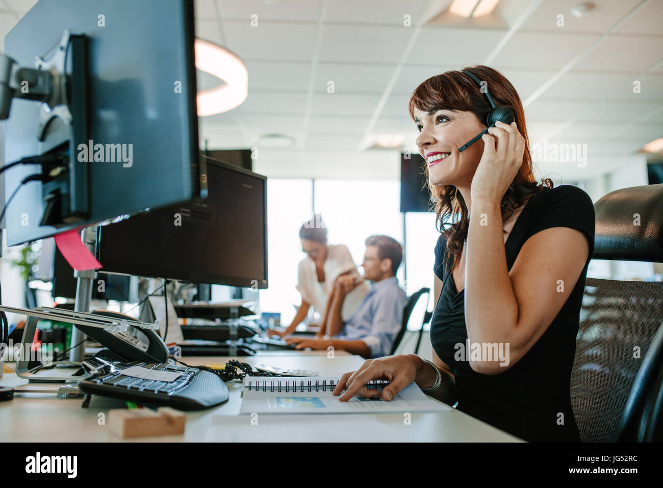 Casual businesswoman working at desk à l'aide d'ordinateur et le casque dans le bureau. L'accent Photo Stock