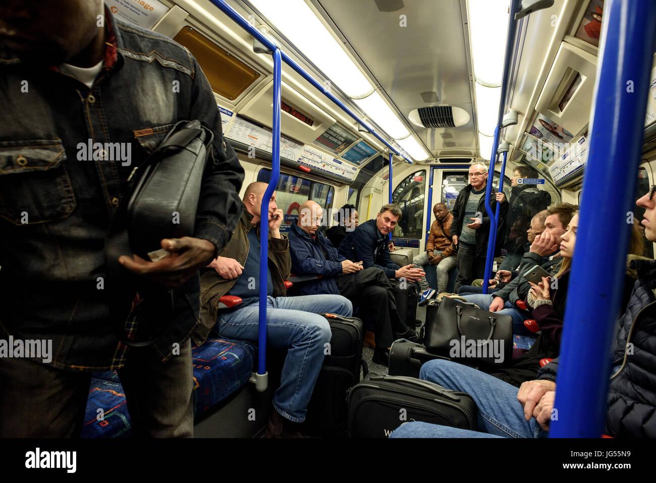 Diverses personnes mixtes sur une circonscription London Underground tube train dans leurs voitures à la fois Photo Stock