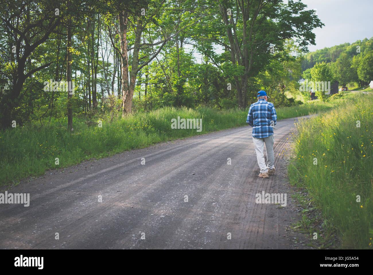 Un vieux homme marche seul sur une route de campagne. Photo Stock