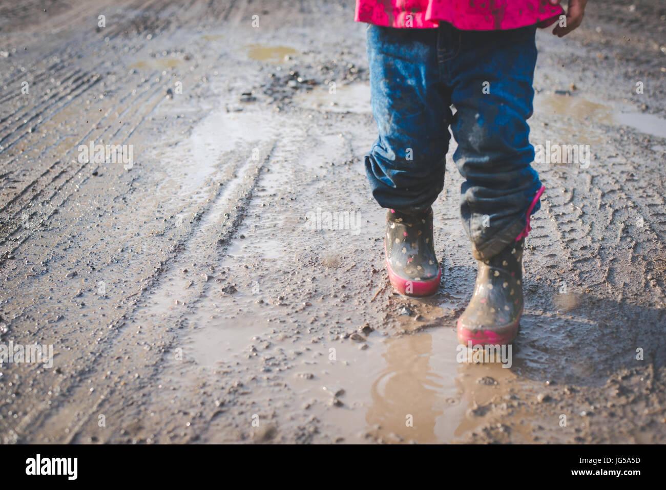 Un enfant marche dans la boue le long d'une route de campagne en Pennsylvanie. Photo Stock