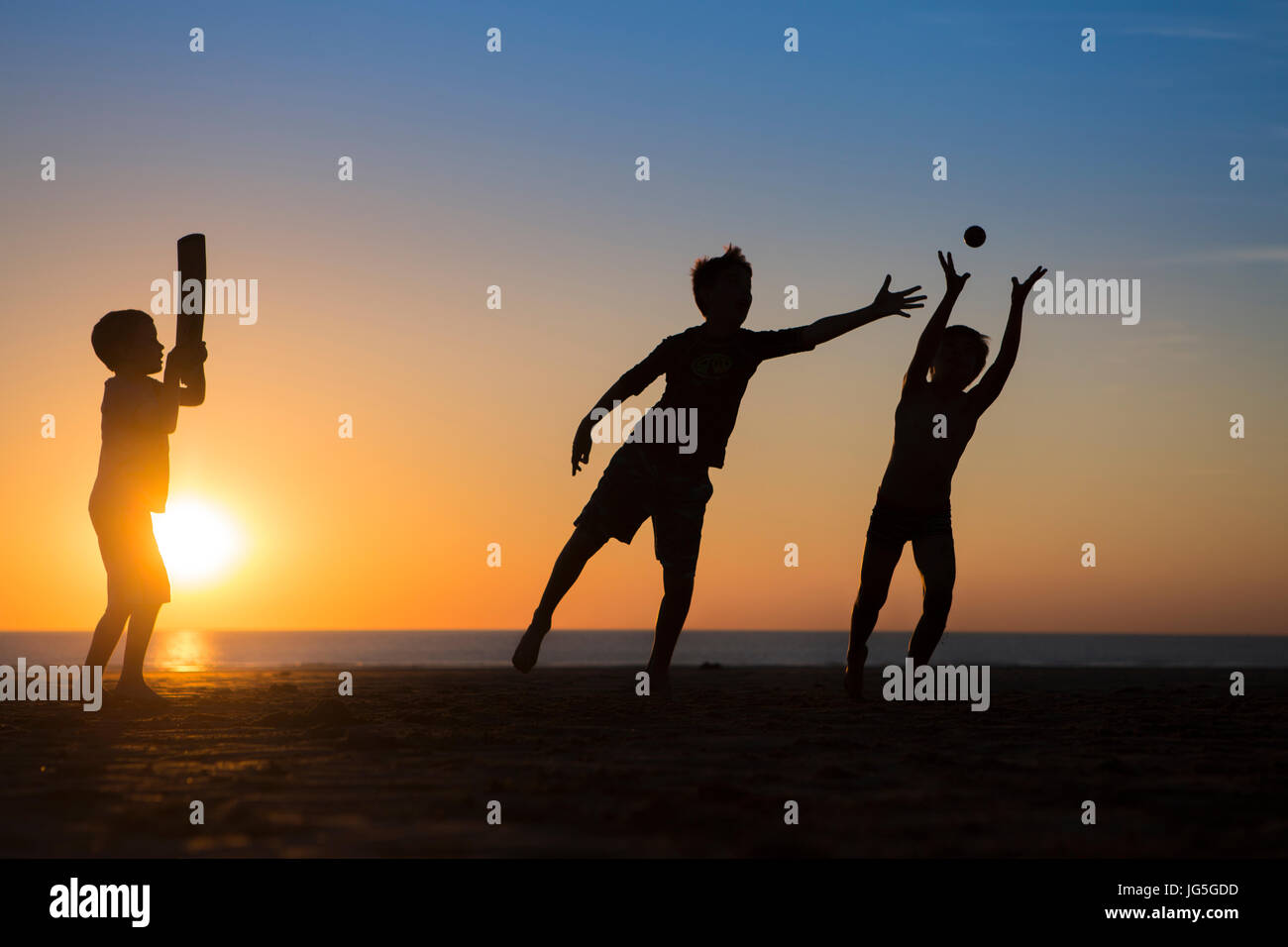 Les enfants jouer au cricket sur la plage au coucher du soleil, Devon, UK Photo Stock