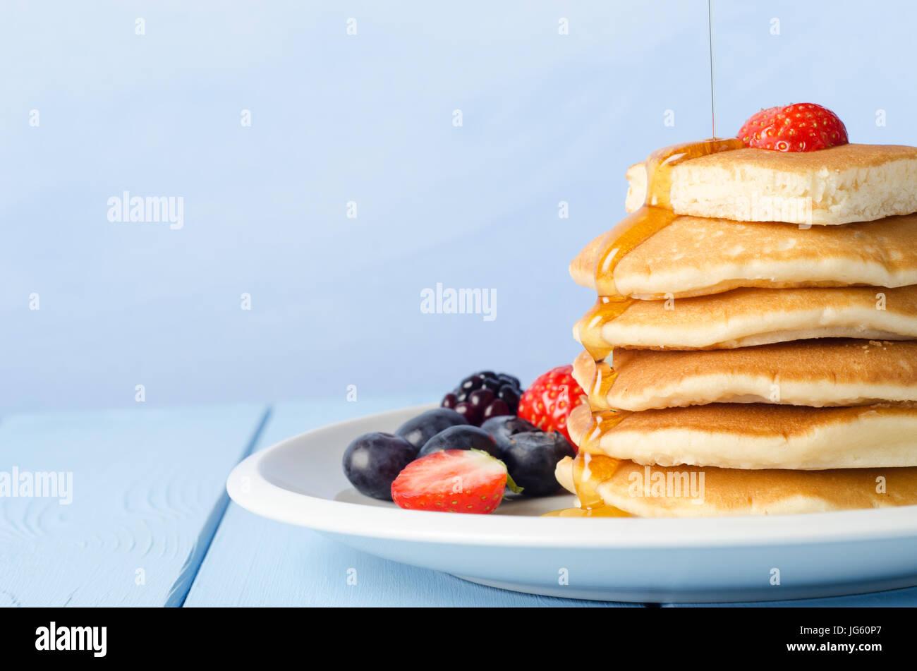 Une pile de crêpes Petit déjeuner garni d'une fraise, debout sur une plaque blanche chine, entouré Photo Stock