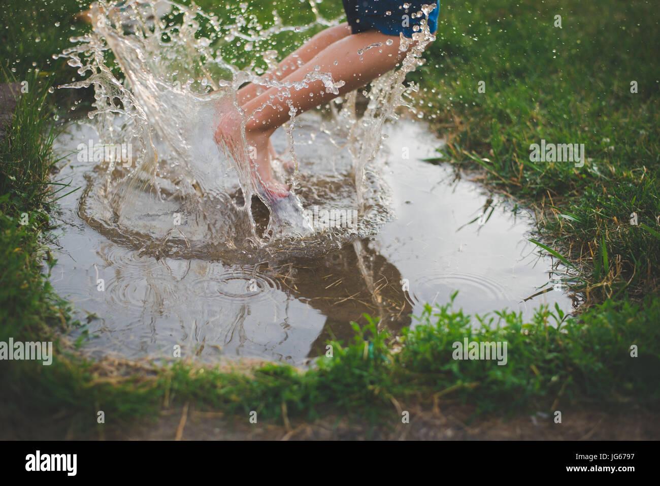 Un enfant saute dans une flaque de boue avec les éclaboussures d'eau autour de ses pieds. Photo Stock