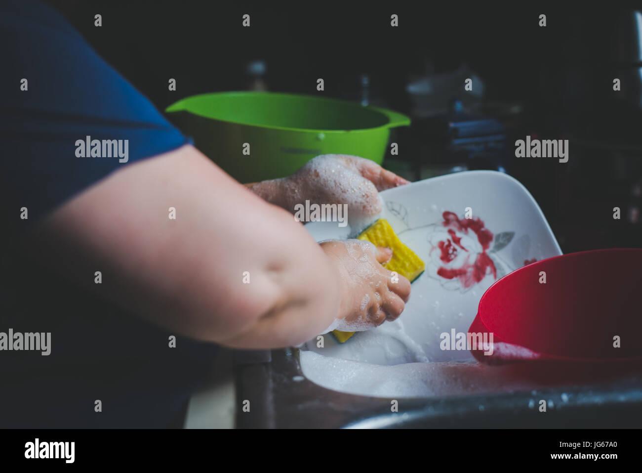 Une femme lave-vaisselle à l'évier. Photo Stock