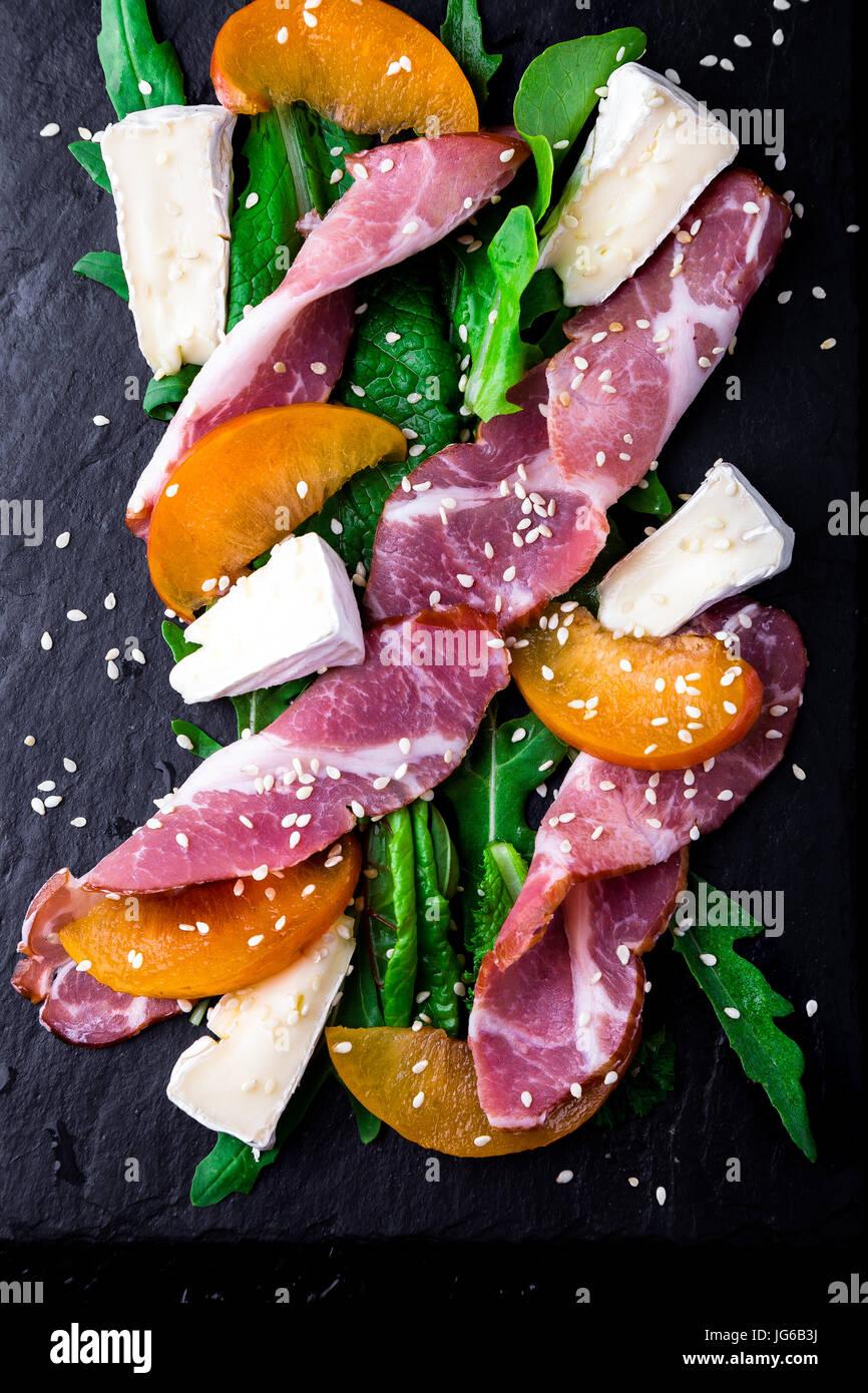 Salade avec du jambon jamon serrano, camembert, melon, roquette sur la plaque d'ardoise noire sur fond noir. Photo Stock
