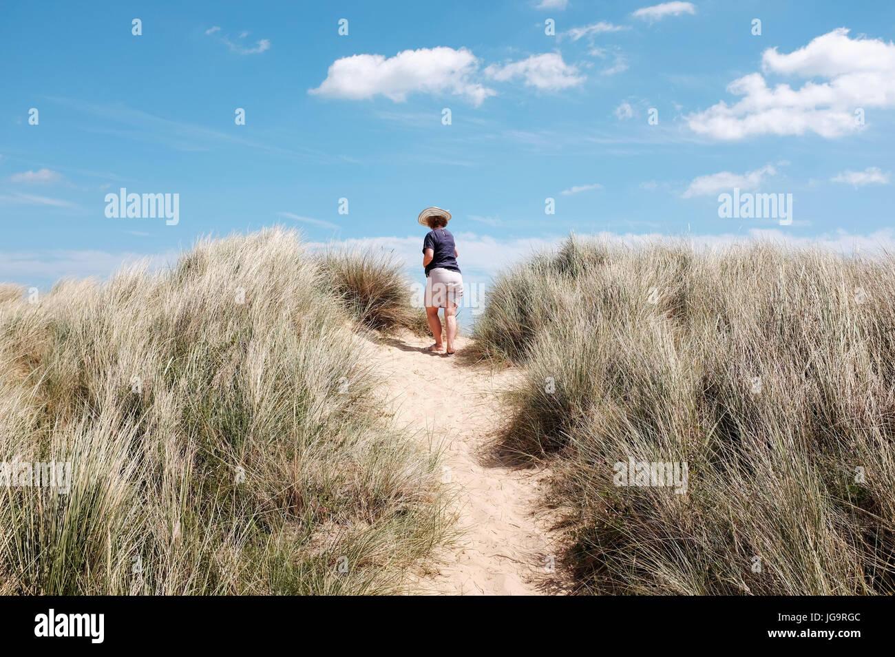 Suffolk Southwold UK Juin 2017 - Femme avec chapeau de soleil sur plage de Southwold et des dunes de sable Photo Banque D'Images