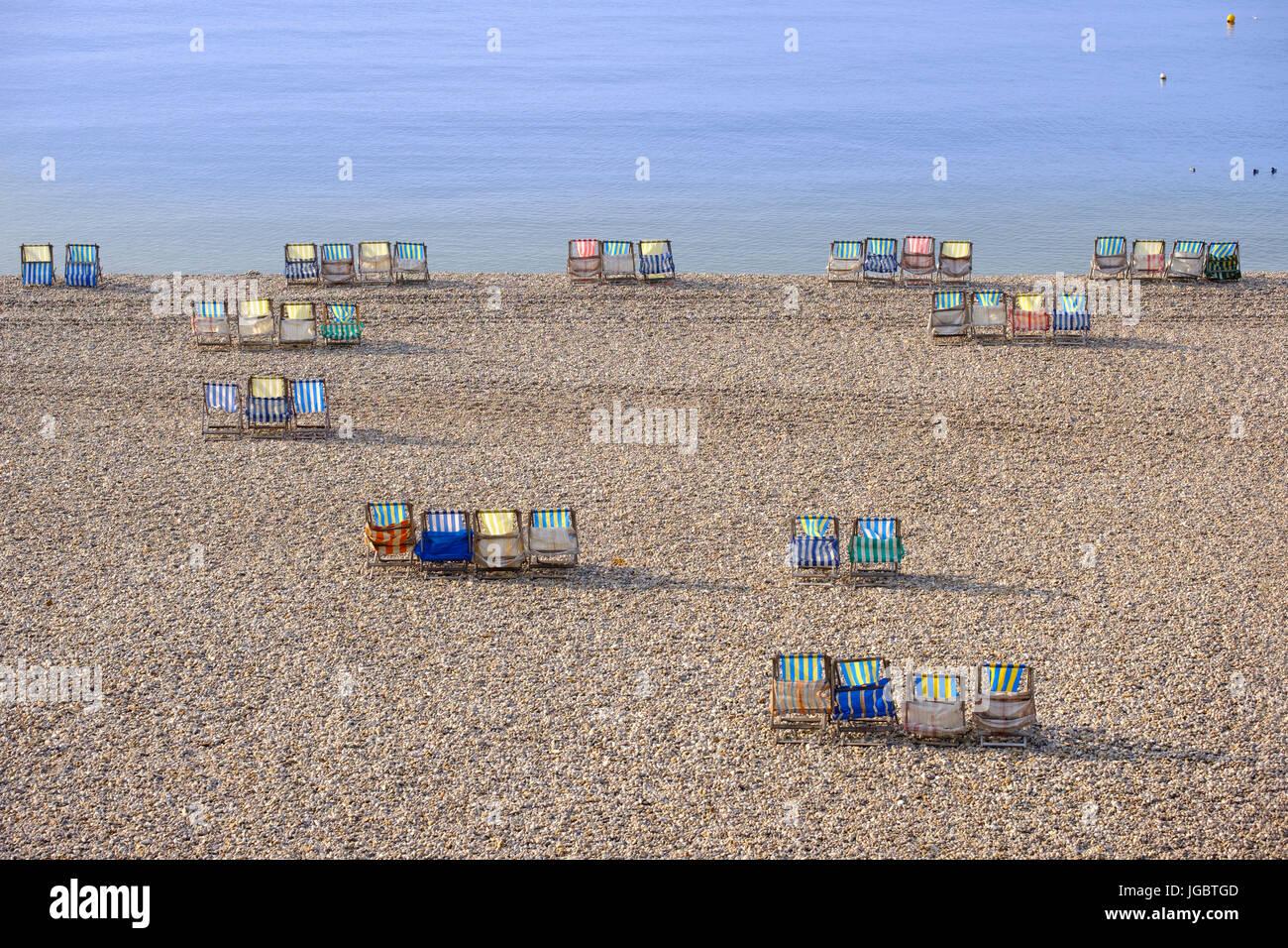 Chaises en toile colorée à la plage de galets, de la bière, de la Côte Jurassique, Devon, Angleterre, Photo Stock
