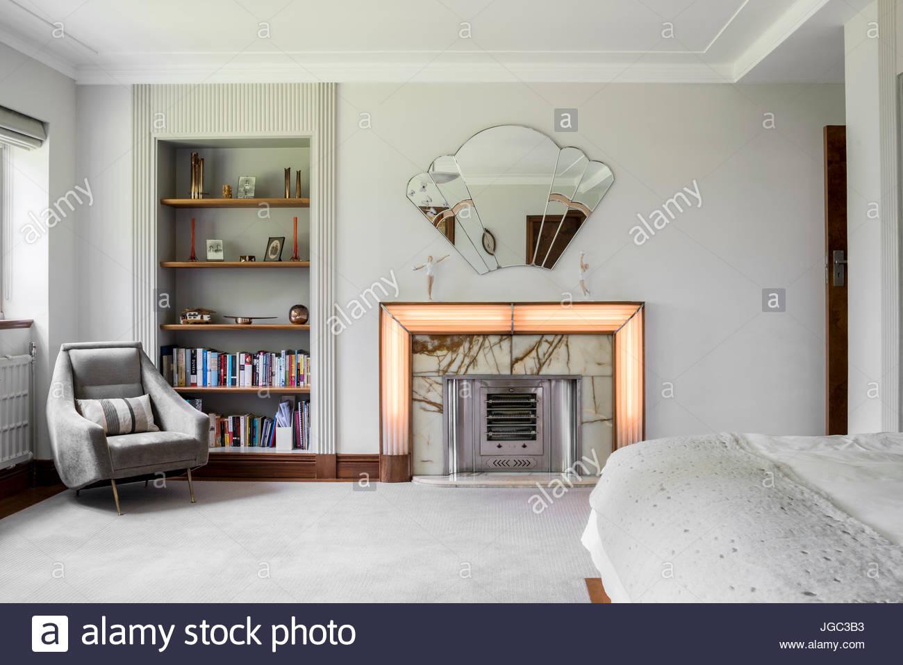 Fauteuil gris clair et des étagères à côté cheminée Art déco et ...